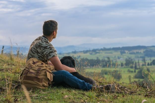Hombre descansando en la cima de una montaña con su perro