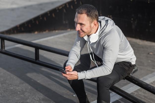 Hombre descansando sobre una baranda y sosteniendo un teléfono