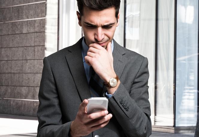 Hombre desconcertado usando su teléfono móvil