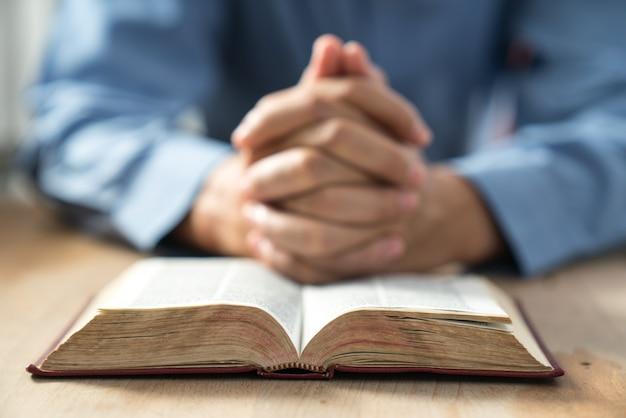 Un hombre desconocido sosteniendo una biblia en sus manos y oró.