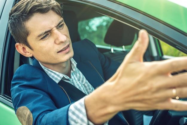 Hombre descontento en un embotellamiento en un automóvil en la carretera