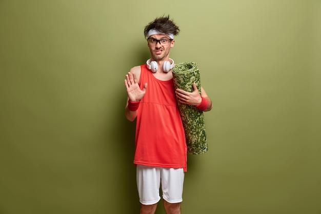 El hombre descontento emocional hace un gesto de parada, pide que no lo molesten, sostiene karemat enrollado, se mantiene en buena forma física, va a hacer ejercicio en el gimnasio, posa contra la pared verde. concepto de deporte