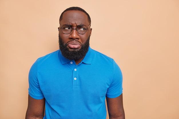 El hombre de descontento infeliz tiene una expresión de mal humor que quiere llorar debido a problemas, los labios, los bolsos, mira hacia otro lado, usa grandes gafas, camiseta azul básica informal aislada sobre una pared marrón