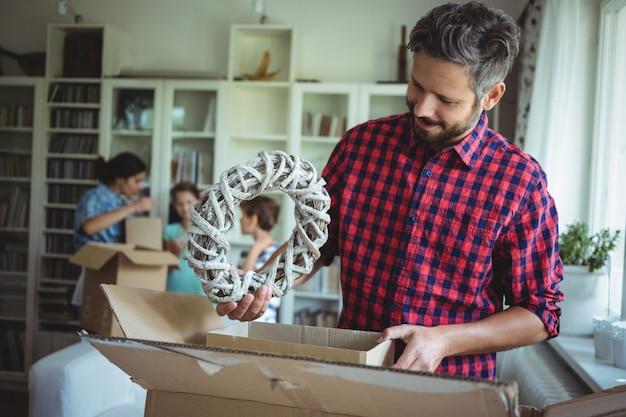 Hombre desempacando cajas de cartón mientras la familia de pie en el fondo