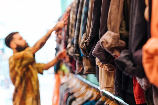 Hombre desenfocado eligiendo camisa de la barandilla en la tienda