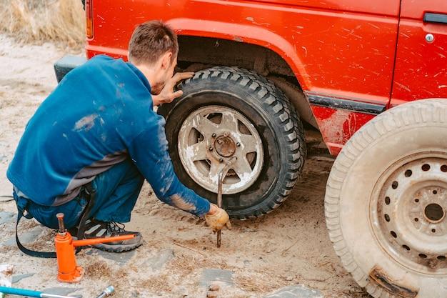 El hombre desenrosca los tornillos de la rueda