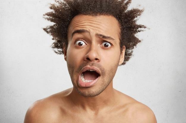 Hombre desesperado con cabello tupido y nítido se ve con ojos saltones y labios curvos
