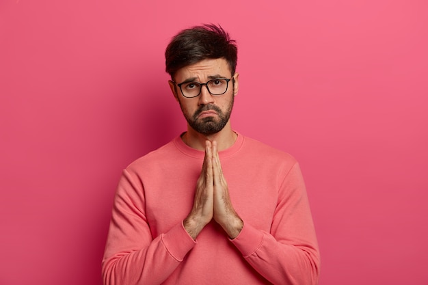Hombre desesperado, culpable y sin afeitar, muestra las manos entrelazadas, pide perdón por su grave error, pide ayuda, parece infeliz, usa anteojos y un jersey informal, posa en el interior sobre una pared rosada.