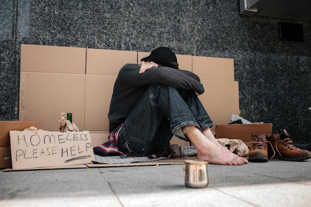 Hombre desesperado sentado en el cartón y ocultando su rostro