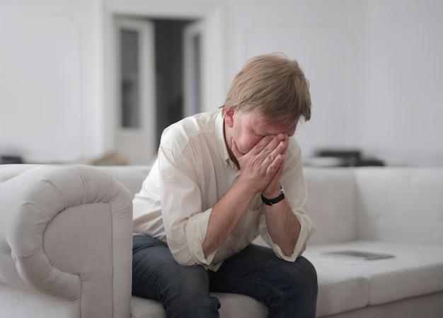 Hombre desesperado sentado en casa