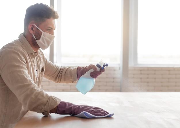 Hombre desinfectando la superficie de madera