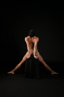 Hombre desnudo descansando las manos sobre la silla y separando las piernas