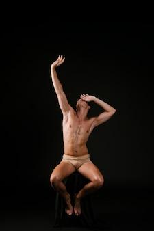 Hombre desnudo en silla sosteniendo la cabeza en la frente