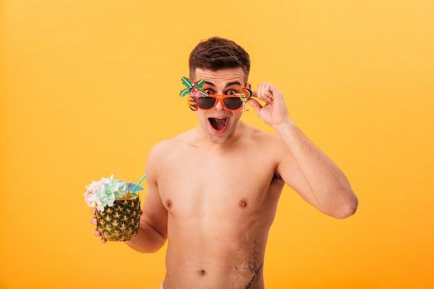 Hombre desnudo sorprendido en pantalones cortos y gafas de sol inusuales con cóctel