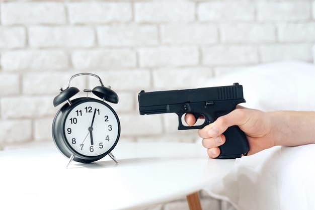 El hombre despertado está apuntando el arma al despertador