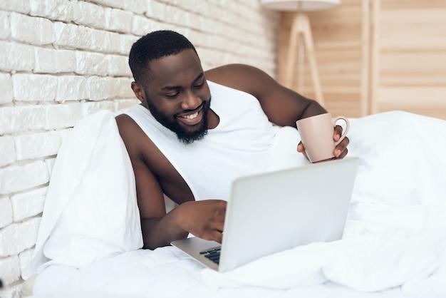 Hombre despierto negro bebe café en la cama mientras trabaja