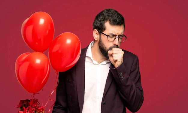 El hombre en el día de san valentín está sufriendo de tos y se siente mal sobre un fondo rojo