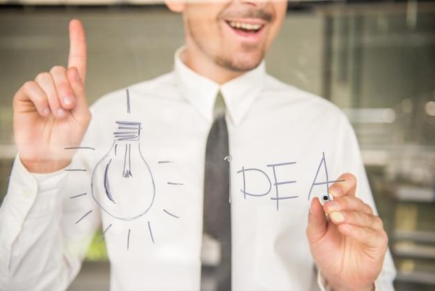 Hombre dibujando una idea en la ventana de cristal en la oficina.