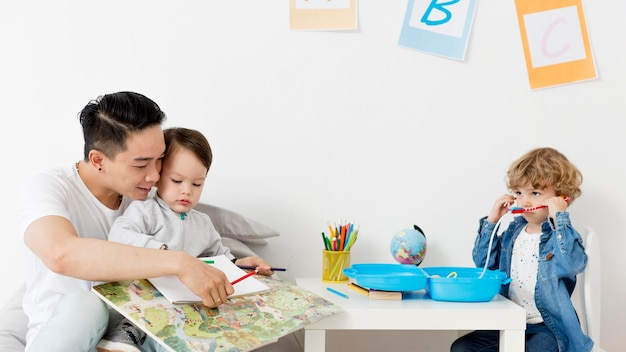 Hombre dibujando con niños en casa