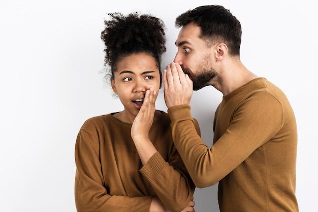 Hombre diciéndole a la mujer un secreto