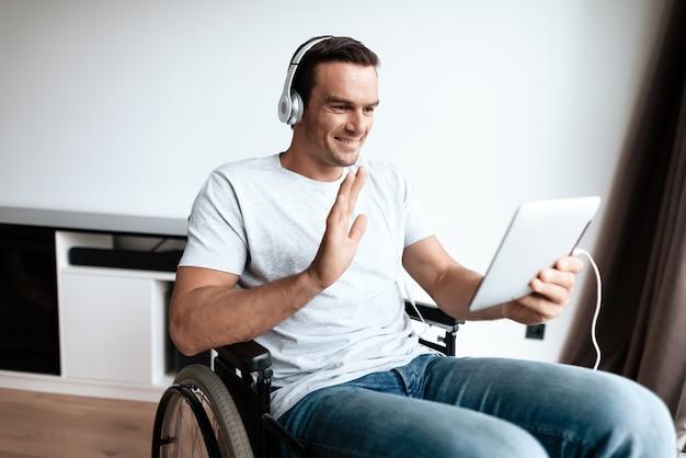 Hombre discapacitado en auriculares comunicarse a través de la tableta.