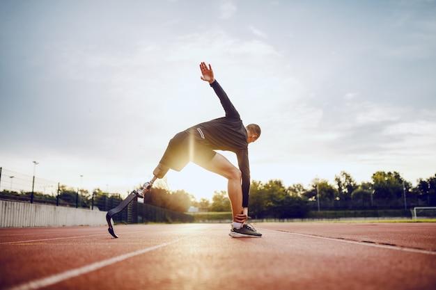 Hombre discapacitado deportivo caucásico guapo altamente motivado en ropa deportiva y con estiramiento de piernas artificiales antes de correr mientras está de pie en la pista de carreras.