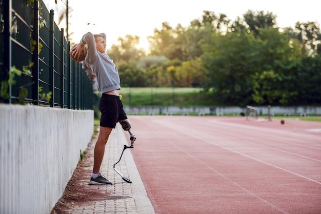 Hombre discapacitado deportivo caucásico guapo de longitud completa en ropa deportiva y con pierna artificial apoyado en la cerca mientras lanza la pelota de baloncesto.