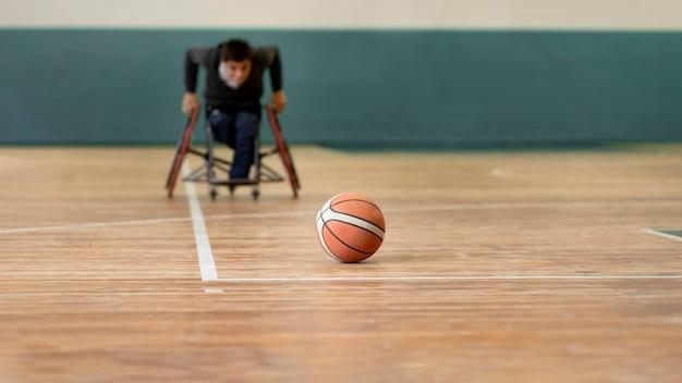 Hombre discapacitado de disparo completo que va después del baloncesto