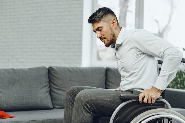 Hombre discapacitado intenta sentarse en un sofá de la silla de ruedas de cerca