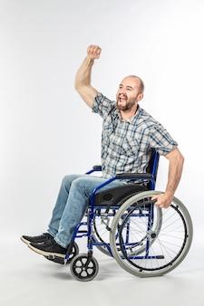 Hombre discapacitado en silla de ruedas con brazo levantado.