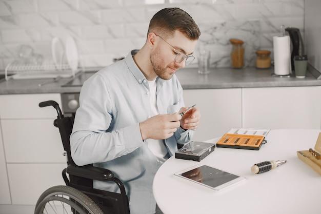 Hombre discapacitado en silla de ruedas como reparación. quedarse en casa, aficiones.