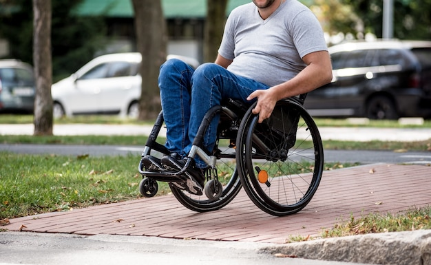 Hombre discapacitado en silla de ruedas cruzando la calle.