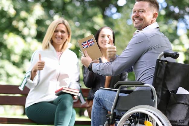 Hombre discapacitado en silla de ruedas está estudiando inglés con amigas en la comunicación del parque y