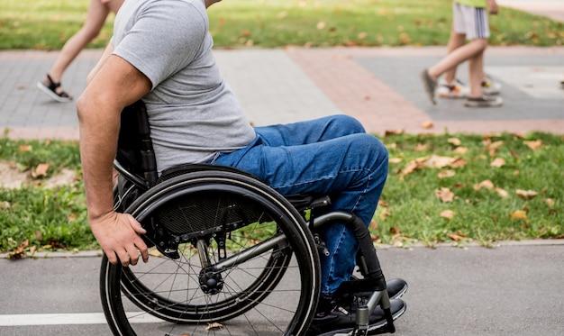 Hombre discapacitado en silla de ruedas a pie en el callejón del parque