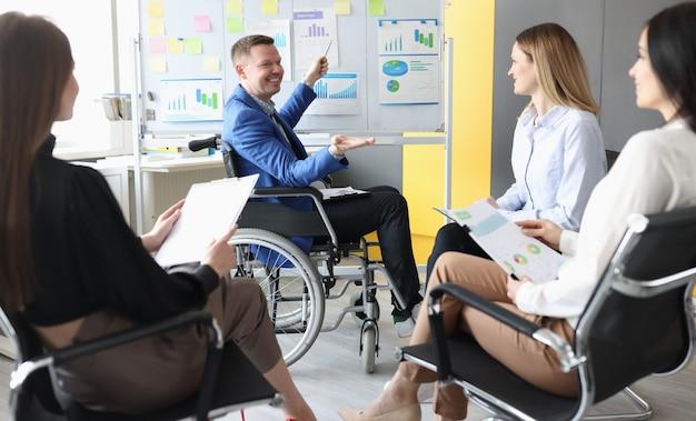 Hombre discapacitado en silla de ruedas que muestra gráficos en la pizarra a sus alumnos