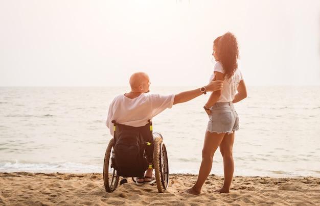 Hombre discapacitado en silla de ruedas con su esposa en la playa.