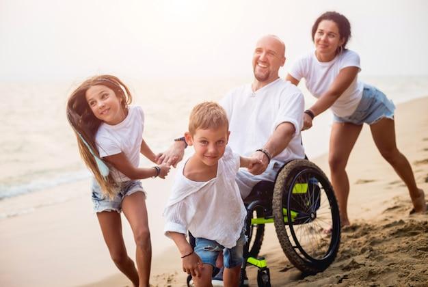 Hombre discapacitado en silla de ruedas con su familia en la playa.