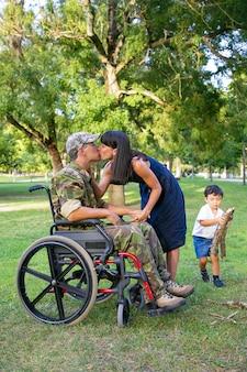Hombre discapacitado en uniforme militar besando a su esposa mientras su pequeño pecado cargando leña para fogata en el parque. veterano discapacitado o concepto de familia al aire libre