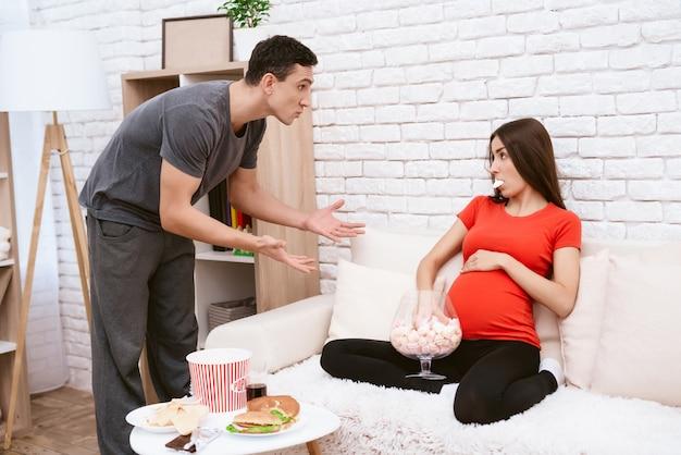 Un hombre discute con una esposa embarazada que come mucho.