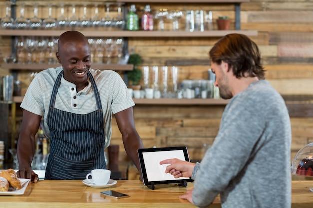 Hombre discutiendo sobre tableta digital con camarero