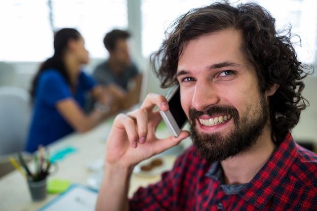 Hombre diseñador gráfico hablando por teléfono móvil