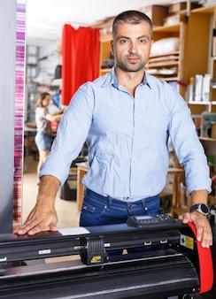 Hombre diseñador y operador de impresión con impresión de papel en la fabricación de impresión