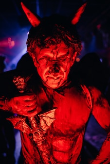 Hombre con un disfraz de miedo y maquillaje en una fiesta de halloween
