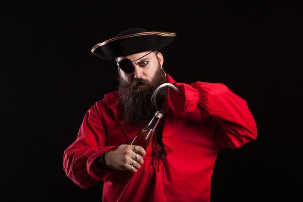Hombre disfrazado de pirata para halloween abriendo una botella con su gancho. hombre guapo disfrazado de pirata.