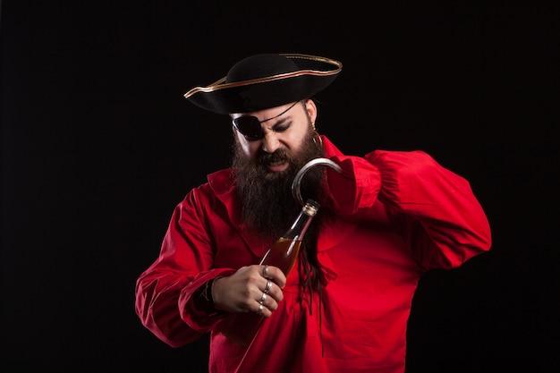 Hombre disfrazado de pirata para halloween abriendo una botella con su gancho. hombre con sombrero de pirata. hombre con ropa de pirata.
