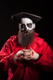 Hombre disfrazado de pirata peligroso para halloween sobre fondo negro.
