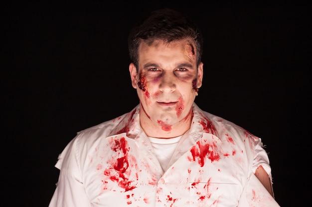 Hombre disfrazado de zombi para halloween sobre fondo negro.