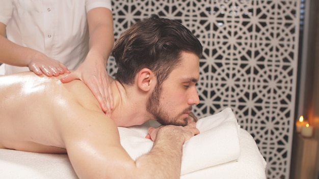 El hombre disfruta de un masaje en un spa después de una semana laboral
