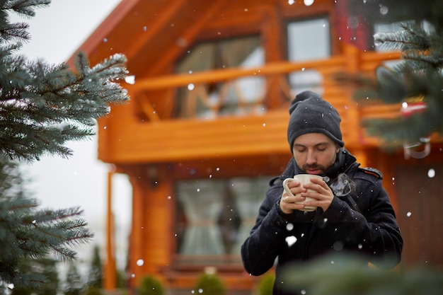 Hombre disfrutando de un café caliente en la terraza nevada