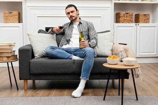 Hombre disfrutando de una cerveza y viendo la televisión tiro largo